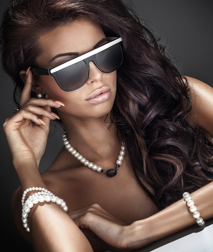 Portrait of beautiful woman with curly long hair wearing sunglasses and jewelry.